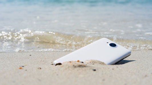phone discarded in sand