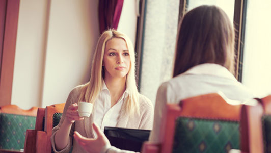woman holding small cup listening to another person talk