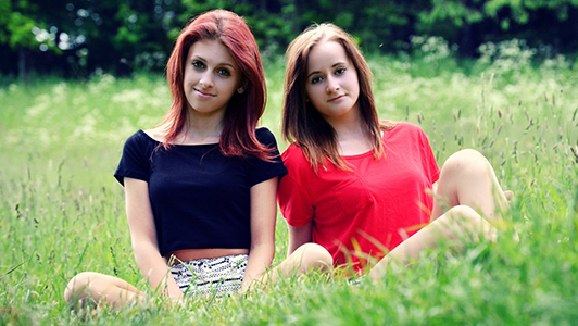 Two girls sitting in the meadow.