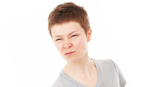 A woman with short hair frowning.