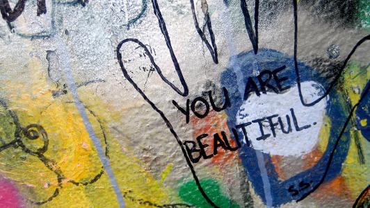 Grafiti shaped like hand saying 'You're beautiful'.