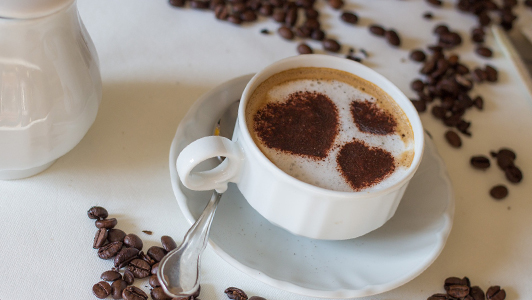 A cup of coffee with hearts made of ground coffee on top of the foam.