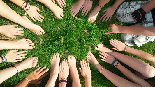 Hands and feet forming a circle on grass