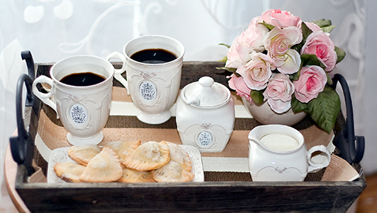 Two cups of coffe, sugar bowl, cookies, and flowers on a platter.