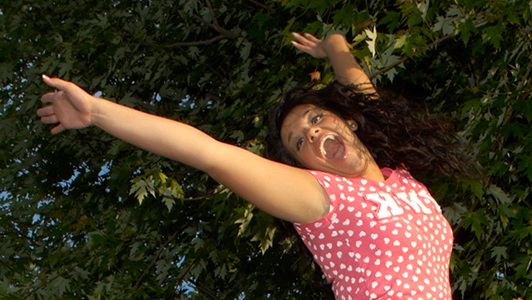 Girl in a pink shirt jumping and laughing.s