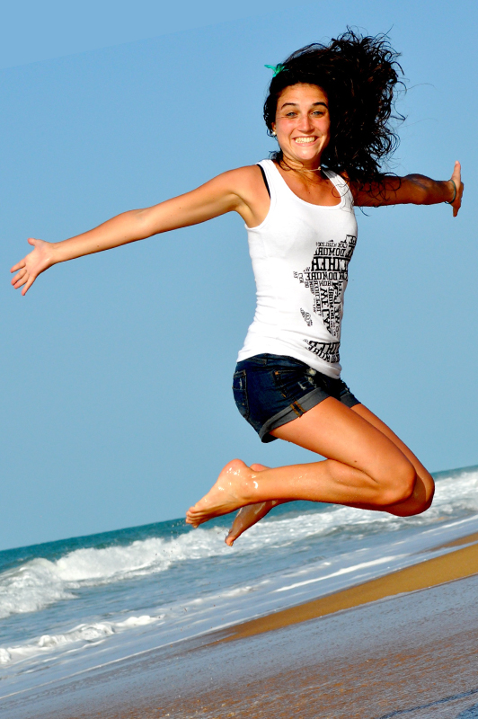 Girl on a beach wearing denim shorts and white top while jumping.