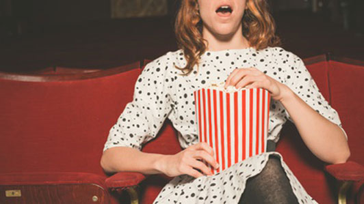 young woman in theater watching moving eating popcorn