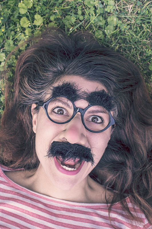 Wacky girl with glasses and fake moustache