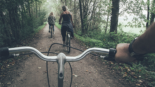 Two girls riding a bike in the forest
