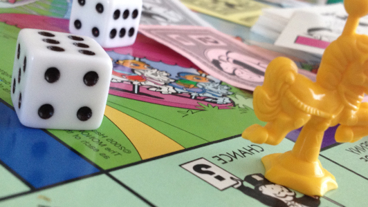 Two die on a Monopoly board.