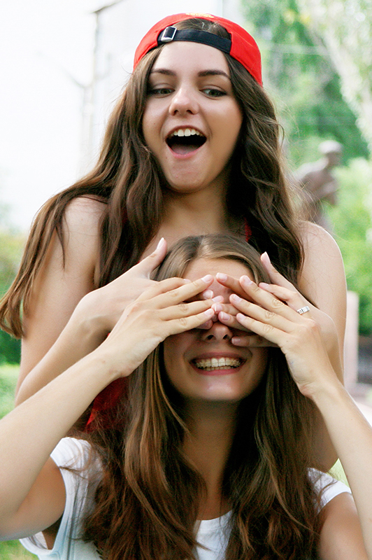 Two girl with long hair, one covering the eyes of the other.