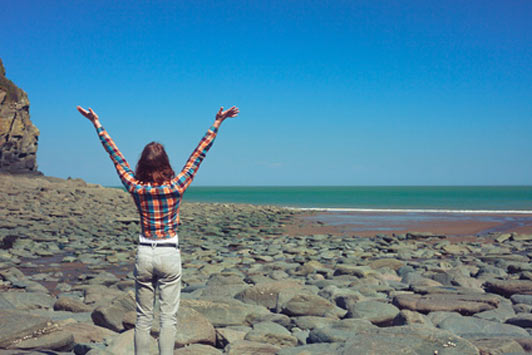 woman with arms wide open at beach