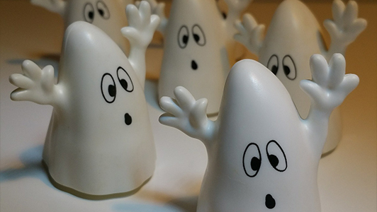 Little toys shaped like ghosts with raised hands.