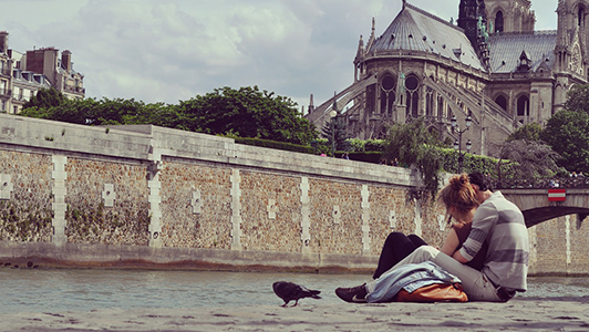 A couple sitting near the river in Paris, a black raven next to them.