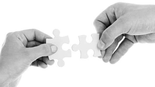 Two hands holding a puzzle piece each.