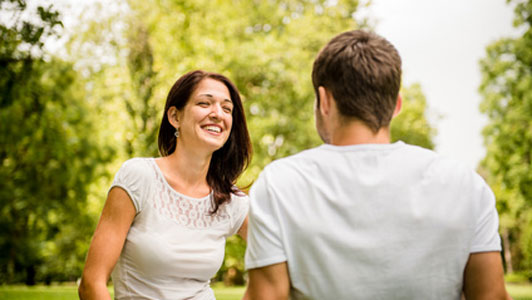 couple in white shirts enjoying talk in park