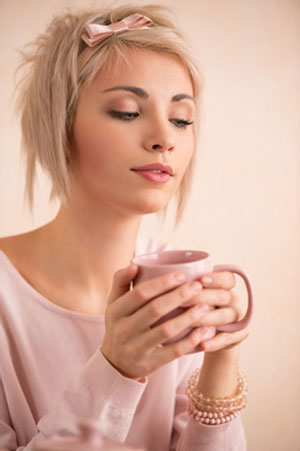 woman looking into coffee cup