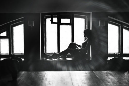 black and white image of girl looking out window