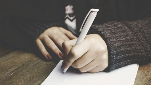 woman in grey sweater taking notes with white pen