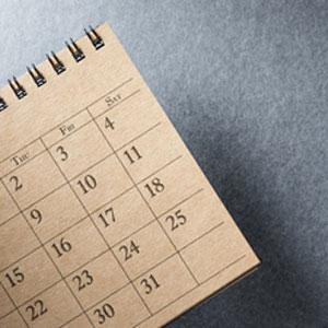 brown desk calendar on grey background