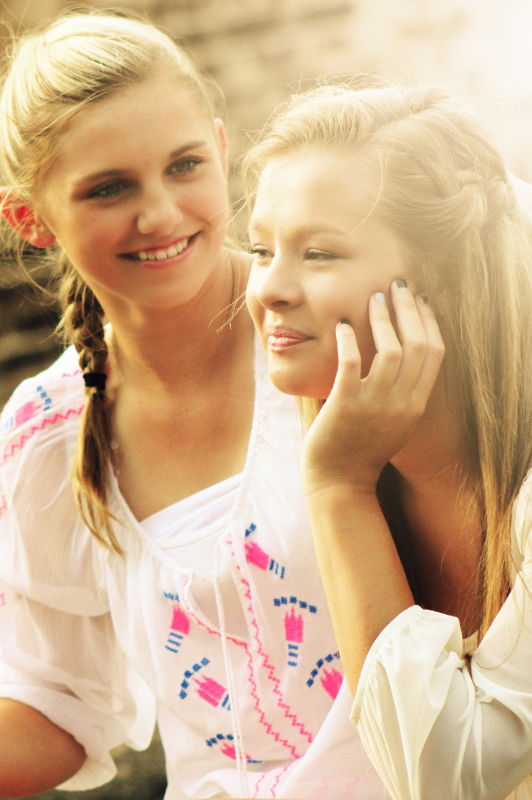 Two teens in white tops smiling.