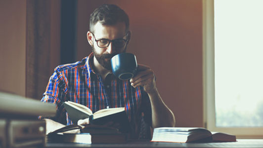 guy with beard with glasses drinking coffee and reading a book at desk