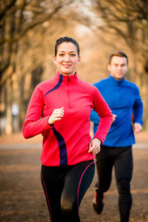 woman in red jogging in front of man in blue
