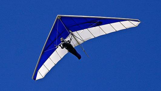 Man hang-gliding over city