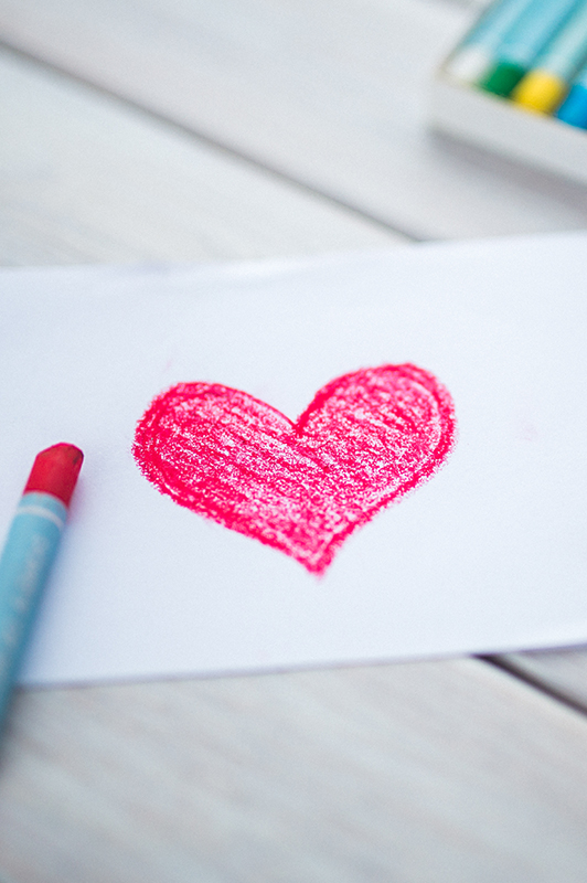A drawing of a heart and a crayon laid next to it