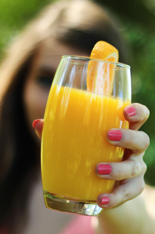 woman holding cup of orange juice
