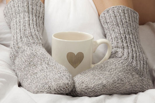 woman in grey socks hugging coffee cup with feet