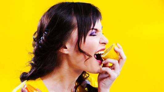 woman biting into lemon