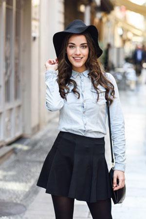 women in long sleeve denim shirt wearing black skirt