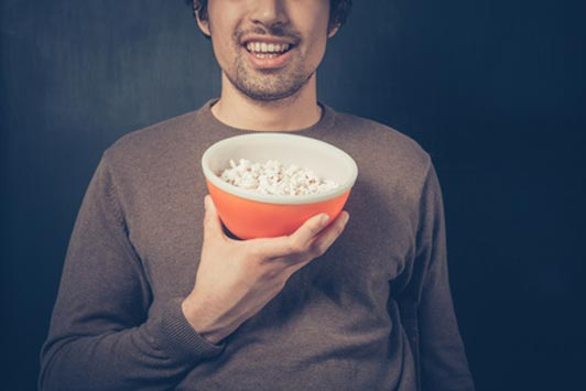 guy holding bowl of popcorn