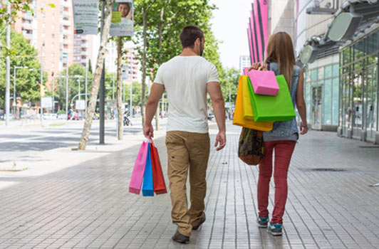 man following woman carrying her shopping bags