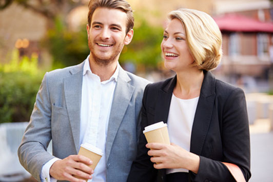 couple dressed up in suits walking down street holding coffee cups