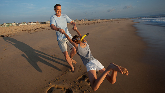 Guy spinning a girl on the beach.