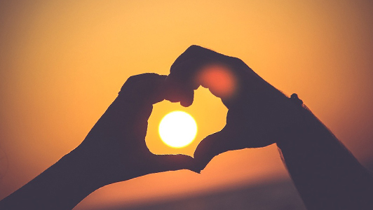 Couple holding hands in a sunset in the shape of heart