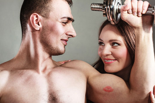 woman's kiss on man's bicep living dumbbell