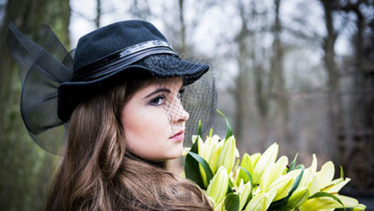 woman in black hat holding flowers