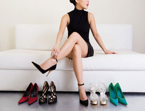 woman wearing black high heels sitting on white couch along side of other footwear