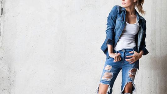 woman in denim jacket wearing jeans with tears