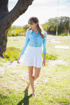 woman standing in grass wearing denim long sleeve shirt and white skirt