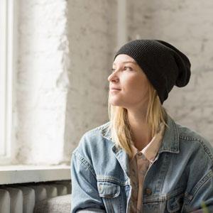woman in oversized denim jacket wearing black hat