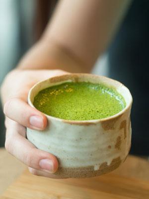 woman holding macha green tea