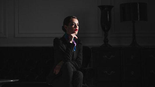 woman in black suit sitting in dark room