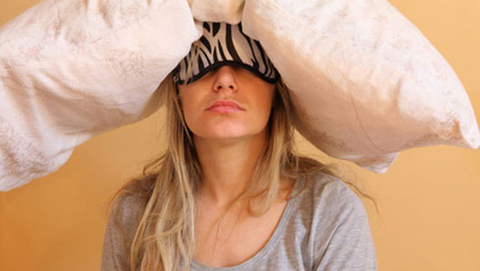 woman waking up with pillow on head