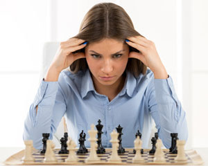 woman sitting in front of chess board