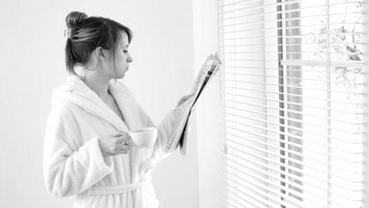 woman holding a cup of coffee standing in front of window in bathrobe reading newspaper