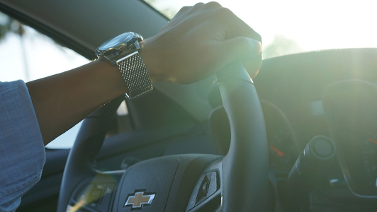 Close-up of a girl's arm with an expensive looking watch holding a steering wheel.